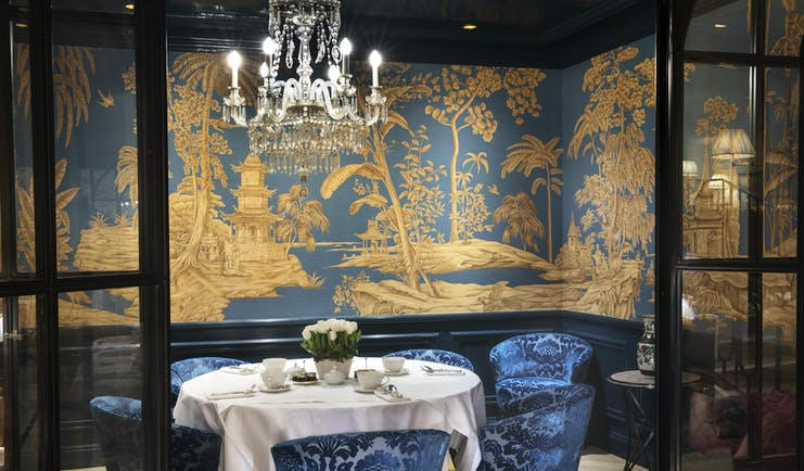 Restaurant with table set up for dining with chandelier and blue velvet chairs
