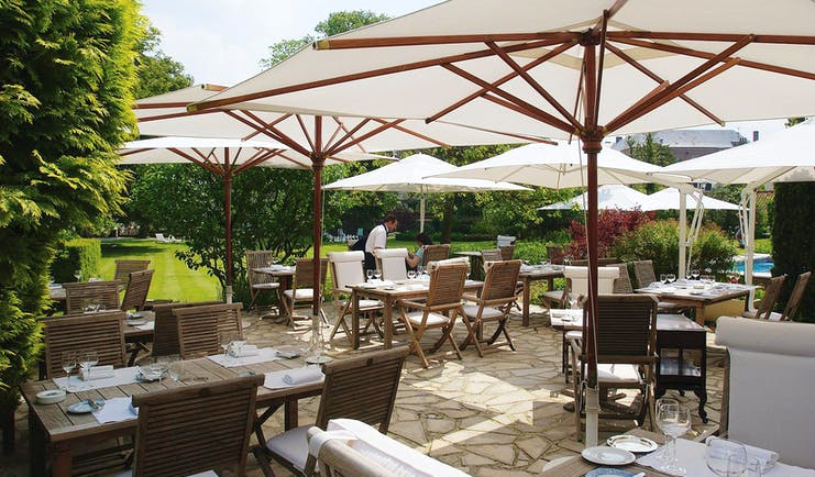 Outdoor dining area with tables and chairs set out on a terrace and white umrbellas shading them