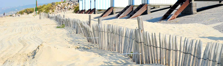 Pastel coloured wooden beach huts on the sandy beach at Hardelot in Pas de Calais