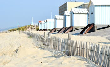 Pastel coloured wooden beach huts on the sandy beach at Hardelot in Pas de Calais