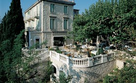 Exterior of the Auberge de Noves in Provence with stone building, large trees surrounding it and a outdoor patio area