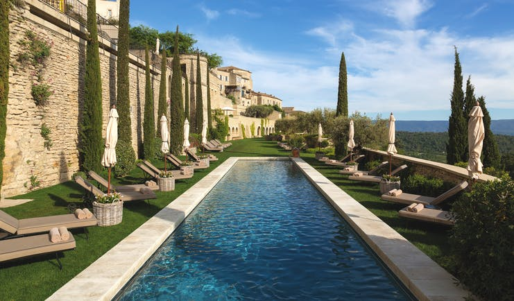 La Bastide de Gordes Provence outdoor swimming pool with sun loungers umbrellas and lawn area