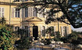 Chateau de Mazan Provence exterior terrace yellow building with shutters terraced seating area with trees and shrubs