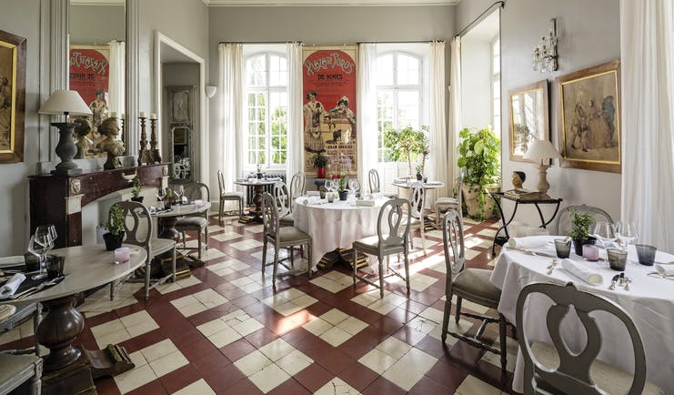 Chateau de Mazan Provence restaurant dining area with a red and white tiled floor and a large red poster