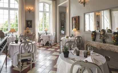 Chateau de Mazan Provence restaurant dining area with a side table with a bust and two vases