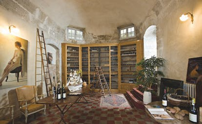 Chateau de Mazan Provence wine cellar with small ladders a chair and table with wine bottles