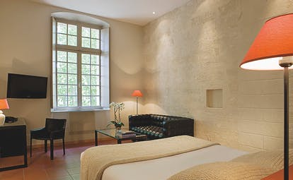 Le Cloitre Saint Louis Avignon bedroom with stone walls black sofa television and desk