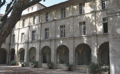 Le Cloitre Saint Louis Avignon exterior building with large arched windows and a tree