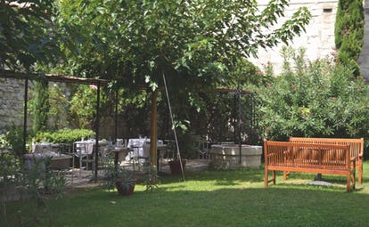 Le Cloitre Saint Louis Avignon garden with seating area and two wooden benches