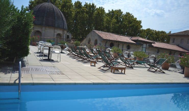 Le Cloitre Saint Louis Avignon rooftop pool with several wooden sun loungers
