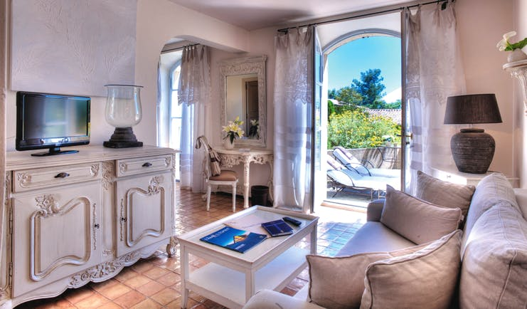 Domaine de Capelongue Provence sitting room sofa cabinet and television door to a terrace with loungers