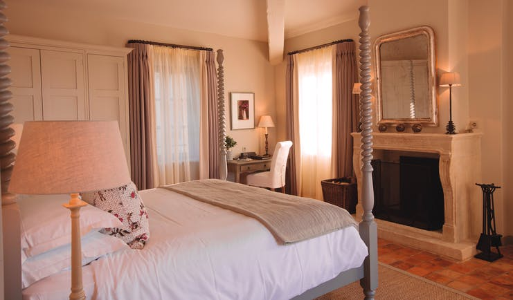 Hotel Crillon le Brave Provence bedroom with large bed with spiral posts and a large mirror over a fireplace
