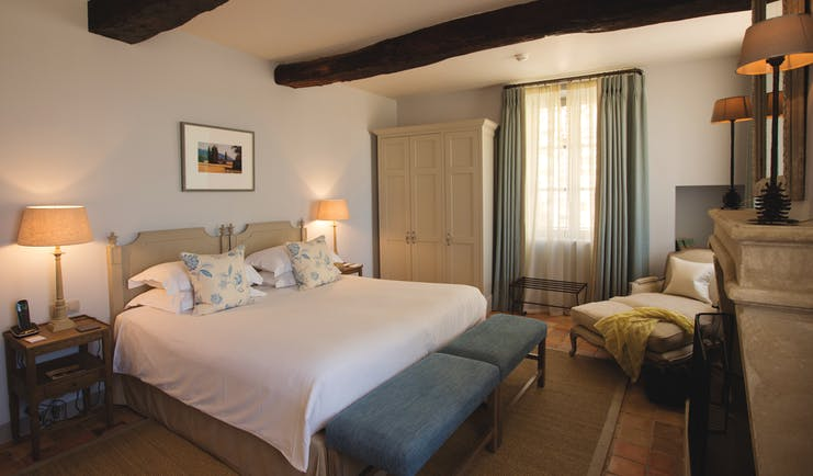 Hotel Crillon le Brave Provence bedroom with exposed beams bedside tables and lamps and an armchair