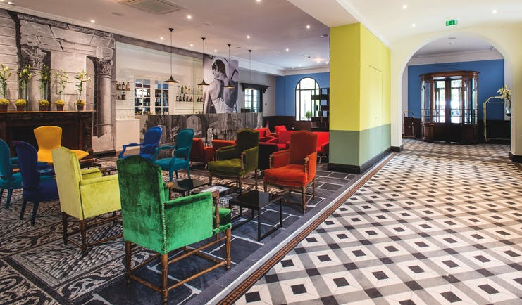 Hotel Jules Cesar Provence bar lounge tiled floor large black and white photograph and several bright chairs
