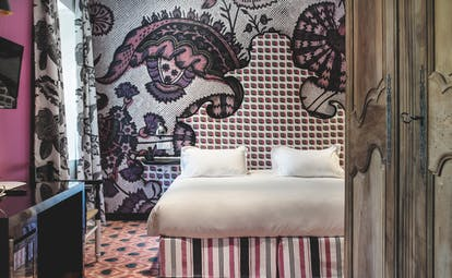 Hotel Jules Cesar Provence bedroom with one bright pink wall and one wall with graphic print patterned carpet
