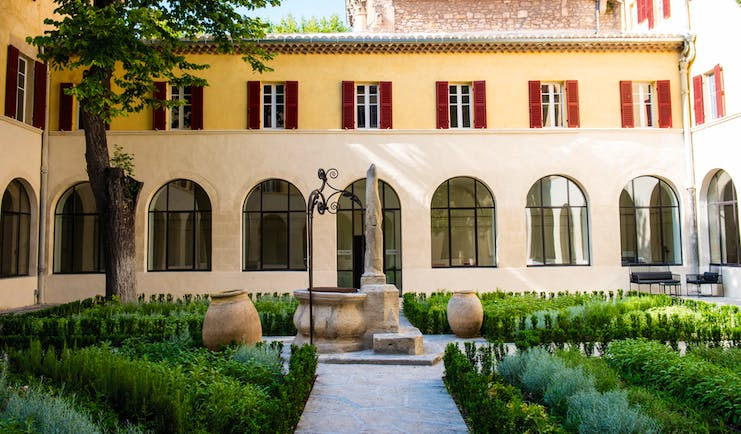 Hotel Jules Cesar Provence exterior courtyard surrounded by a building with large windows topiary and statues
