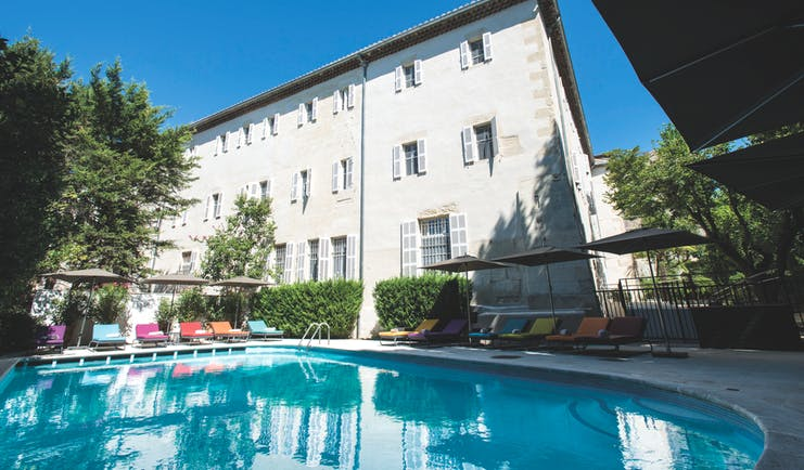 Hotel Jules Cesar Provence outdoor swimming pool with sun loungers and umbrellas overlooked by a white building