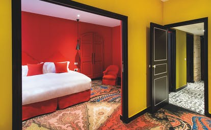 Hotel Jules Cesar Provence red bedroom with archway into a room with yellow walls