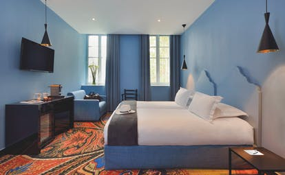Hotel Jules Cesar Provence superior bedroom television desk sofa and a brightly coloured carpet