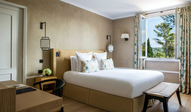 Room with white bed and open window view of trees at le Pigonnet