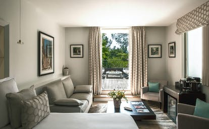 Large room with sofa, neutral tones of furniture, with outdoor terrace at le Pigonnet