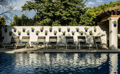 Row of sunbeds by wall next to pool at le Pigonnet