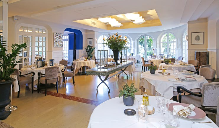 Restaurant with round white table,s wooden floor and glass windows at the pigonnet