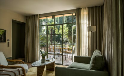 Living room of suite with green sofa and terrace at le Pigonnet