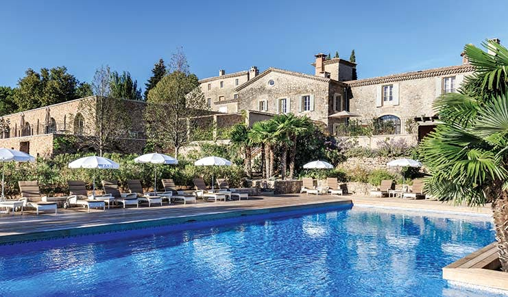 Chateau de Berne Provence exterior pool large stone building sun loungers and umbrellas