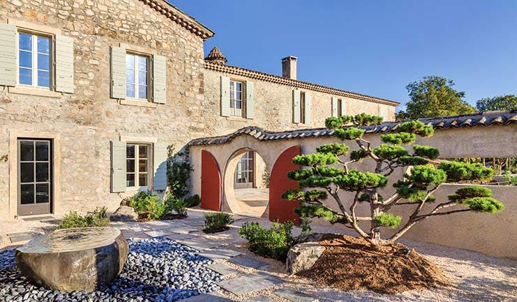 Chateau de Berne Provence exterior stone building with shutters a wall with a round door and a red gate