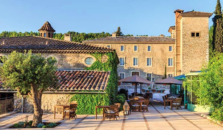 Chateau de Berne Provence outdoor patio stone building with foliage on the walls