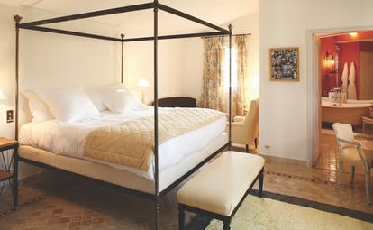 La Bastide de Moustiers Provence aviary bedroom with four poster bed view into a red bathroom