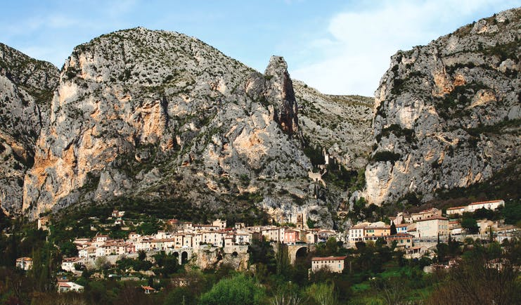La Bastide de Moustiers Provence exterior village with several houses in front of large grey rockface