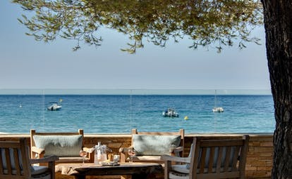 Dining terrace under tree facing the sea at Pinede Plage