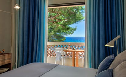 Sea facing room with balcony and blue curtains at Pinede Plage