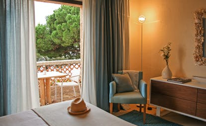 Room with white bedspread with balcony and light on at Pinede Plage