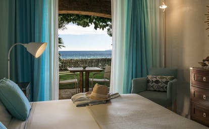 Room sea facing ground floor with terrace and blue curtains at Pinede Plage