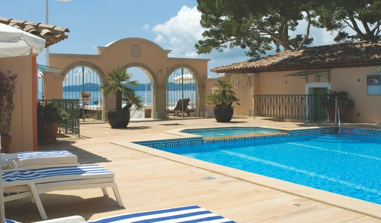 Le Club de Cavaliere Provence outdoor pool overlooking a wall with three arches and the sea