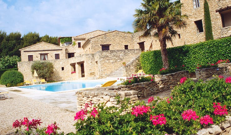 Outdoor area at le mas des herbes blanches with flowers, palm trees and a pool