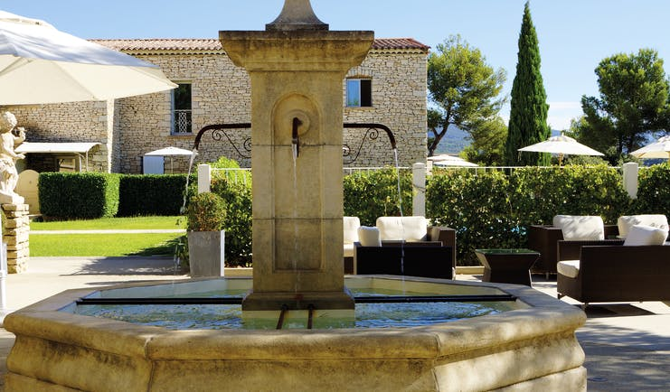Le Phebus courtyard with large fountain in centre, seating areas and  neatly trimmed bushes in the background