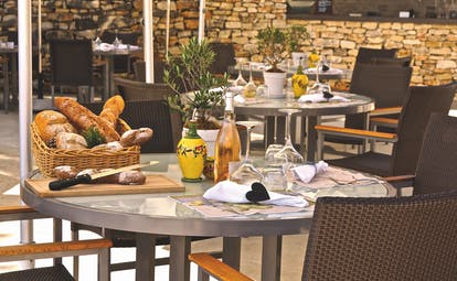 Outdoor dining area with tables set out with baskets of bread on
