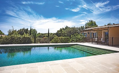 Le Phebus outdoor swimming pool with tiled surface and looking out over greenery