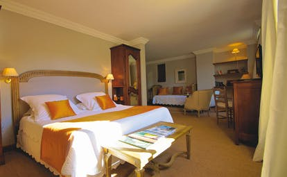 Large room with bed, seating areas and wooden storage units