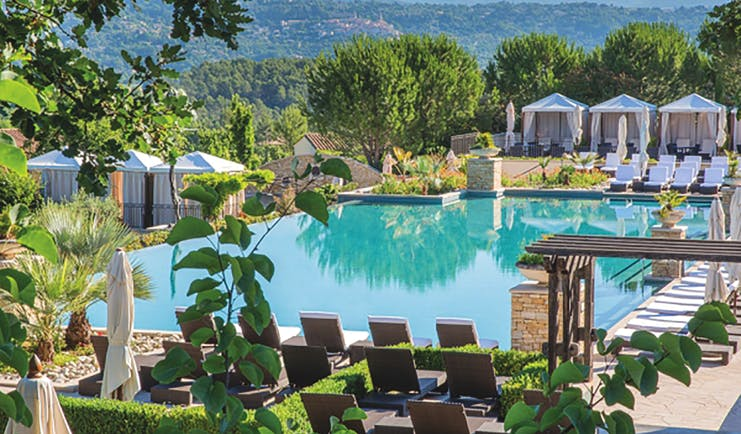 Terre Blanche Hotel and Spa Provence infinity pool with white sun loungers and cabanas