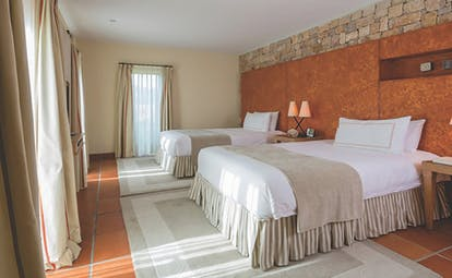 Terre Blanche Hotel and Spa Provence premier suite bedroom with two large beds orange wall and lamps