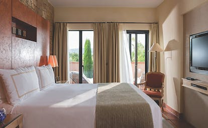 Terre Blanche Hotel and Spa Provence premier villa bedroom with chair and glass door onto a balcony
