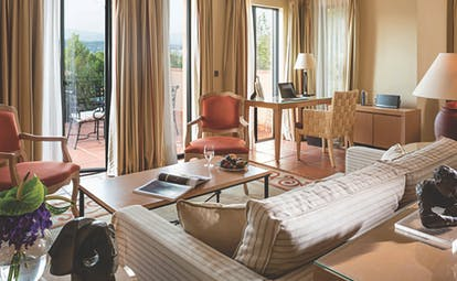 Terre Blanche Hotel and Spa Provence premier villa lounge sofa coffee table two chairs and view onto a patio