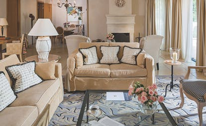 Terre Blanche Hotel and Spa Provence villa lounge sitting room with two sofas patterned rug and fireplace