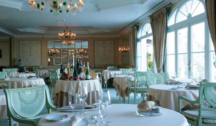 Althoff Villa Belrose Saint Tropez restaurant indoor dining area with chandeliers and large windows