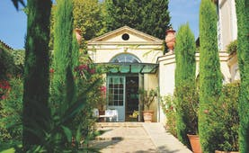 Villa Gallici Provence entrance path with topiary trees and potted plants leading to a building